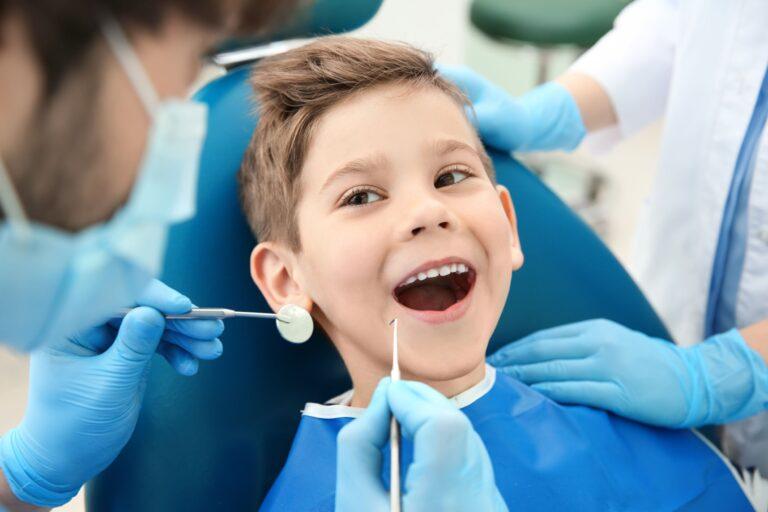 Stomatologia dziecięca - uśmiechnięty chłopiec w czasie zabiegu